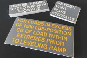 Samples of screen-printed safety and instruction decals for military equipment.