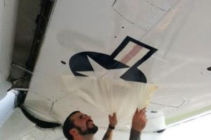 Screen-printed and die-cut decal being applied to military aircraft